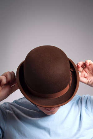 Portrait of man covering his face with bowler hat photo