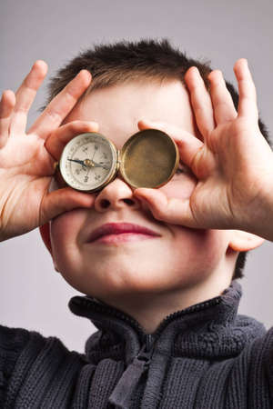 Little boy using compass as eye goggles
