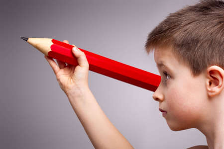 A child concentrates while holding a giant red pencil Stock Photo