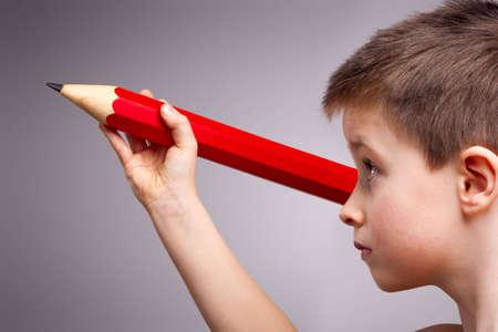 ni�os con l�pices: Un ni�o se concentra en posesi�n de un l�piz gigante rojo