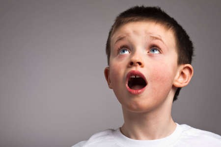 child singing: Little boy looking up in amazement Stock Photo