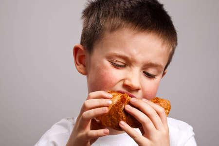 Portrait of a little boy eating a croissant