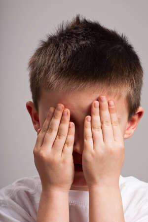 Little boy hiding his face with his hands Standard-Bild