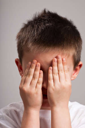 Little boy hiding his face with his hands Stock Photo