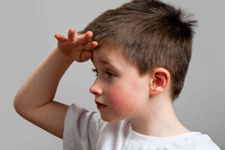 quizzical: Little boy looking with hand above eyes