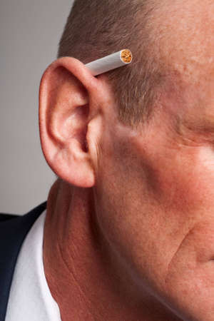 Close-up of business man with cigarette behind his ear photo