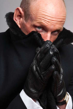only mid adult men: Man in black coat with fur collar covering part of his face