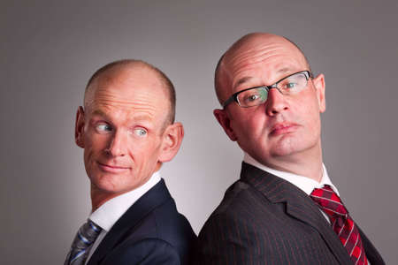 Portrait of two businessmen standing back-to-back
