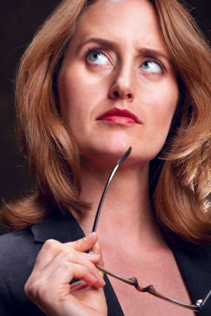 Portrait of serious businesswoman holding eye glasses Stock Photo - 6683425