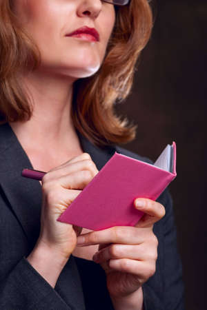 Close-up of woman writing in pink notebook photo