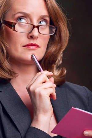 Secretary wearing glasses, holding pen and notebook, looking up photo