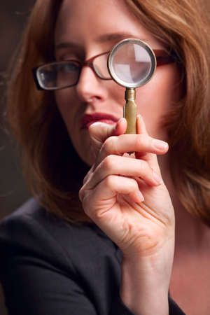 Close-up of woman looking through magnifying glass -- focus on hand Stock Photo - 6683382