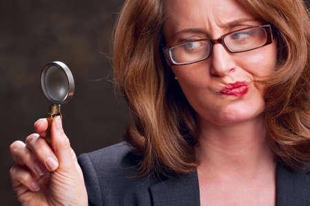 quizzical: Woman holding magnifying glass with quizzical expression