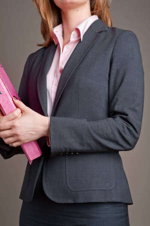 Close-up of anonymous businesswoman, wearing suit and carrying pink file folder