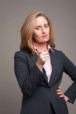 authoritative woman: Businesswoman pointing with stern expression - focus on finger