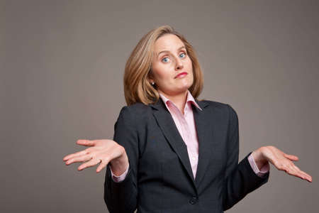shrugging: Businesswoman shrugging her shoulders as if to say whatever