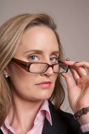 Woman looking over glasses while holding them Stock Photo - 6683327