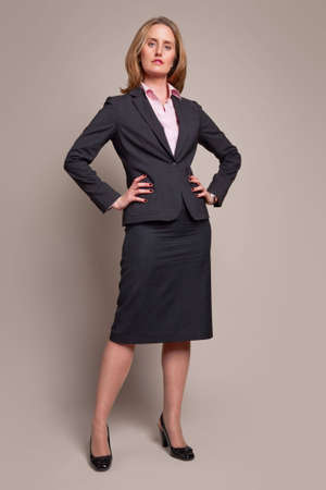 Full-length standing businesswoman with arms Akimbo