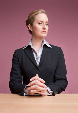 Female presenter sitting at desk with hands clasped Stock Photo - 6683373