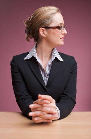 newsreader: Newsreader sitting at desk with hands clasped