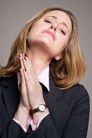 pleading: Portrait of a pleading or praying businesswoman