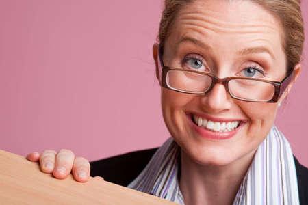 Portrait of fun businesswoman behind desk on pink background Stock Photo - 6743476