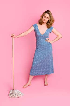 Woman standing with mop, wearing blue dress on a pink background Standard-Bild