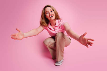 Crouching woman with outstretched open arms on pink background