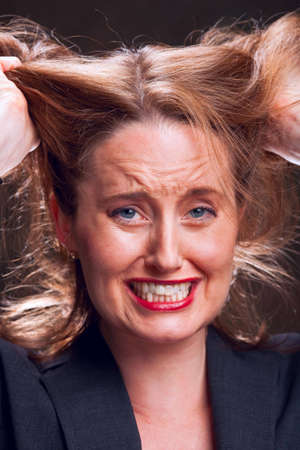pull out: Frustrated businesswoman tearing her hair out