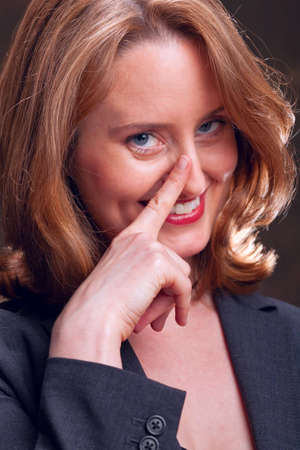 human nose: Portrait of businesswoman with knowing look touching her nose with her finger Stock Photo