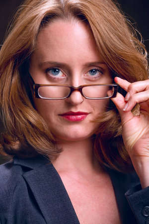 Businesswoman peeking over her eye glasses with stern expression Stock Photo - 6820203