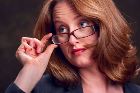 Businesswoman touching her glasses and looking away Stock Photo - 6820221