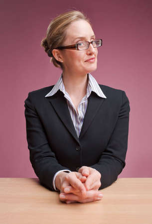 Friendly businesswoman, sitting at desk against a dusty pink background Stock Photo - 6820130