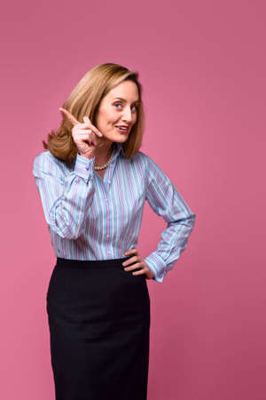 reprimanding: Woman wearing striped button down shirt, wagging finger on pink background