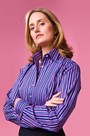 button down shirt: Businesswoman with arms folded wearing striped shirt on a pink background