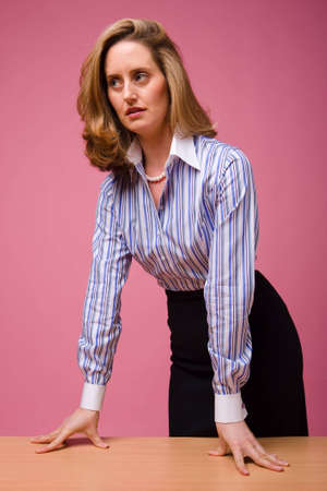 authoritative woman: Authoritative woman in striped shirt, leaning on desk on pink background Stock Photo