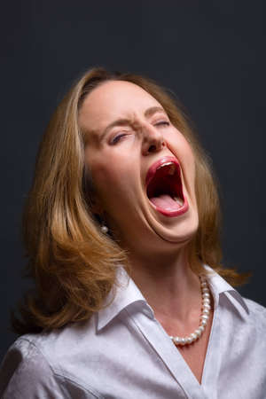 Portrait of woman with open mouth as if shouting, singing or screaming in pain