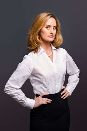 Portrait of a blonde woman wearing a white jacquard shirt on a grey background Stock Photo
