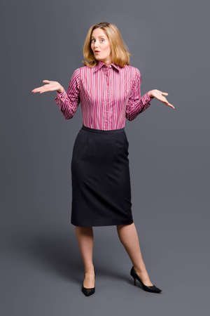 Standing woman wearing striped shirt and shrugging her shoulders photo