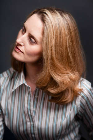 looking away from camera: Portrait of blonde woman, looking away from camera and wearing striped shirt