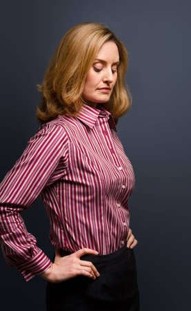 striped shirt: Low key portrait of brooding woman with eyes down