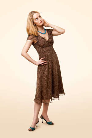 one mid adult woman only: Full-length portrait of classic model wearing brown dress, standing and looking up Stock Photo