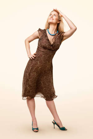Full-length portrait of classic model wearing brown dress and looking up on pale background photo