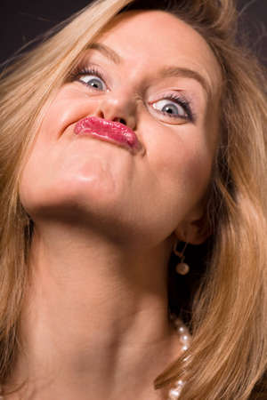 rude: Glamorous blonde woman pulling a silly face Stock Photo