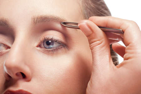health fair: Close-up of woman plucking eyebrow using tweezers