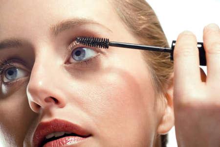Close-up of woman applying mascara on white background photo