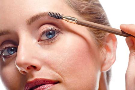 mujer maquillandose: Close-up de mujer aplicar maquillaje con pincel de ceja Foto de archivo
