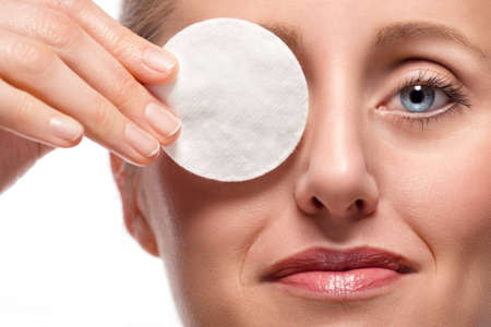 Close-up of woman removing eye make-up using cotton pad