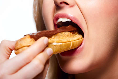 calorific: Close-up of womans mouth eating a chocolate eclair