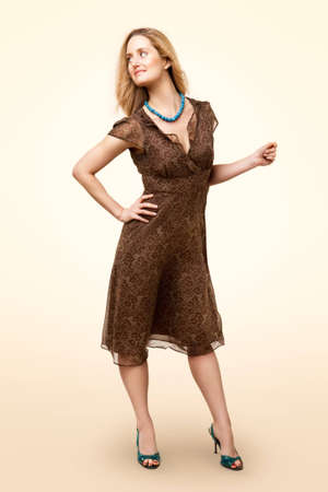 Full-length portrait of classic model wearing brown dress, standing and looking to camera left, isolated on pale background Stock Photo - 7700885